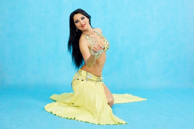 Bailarina encantadora realiza danza del vientre oriental sobre un fondo azul.