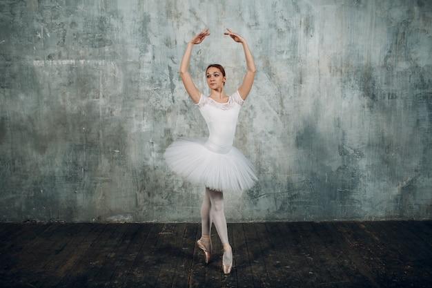 Bailarina femenina. joven hermosa mujer bailarina de ballet, vestida con traje profesional, zapatos de punta y tutú blanco.