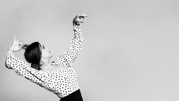 Bailarina flamenca en blanco y negro agachándose con espacio de copia