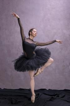 Bailarina de frente con rodilla doblada.