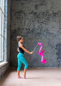 Bailarina de gimnasta profesional bailando con lazo rosa.