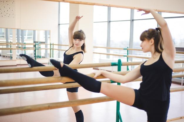 Bailarina está haciendo ejercicios en la clase de ballet.