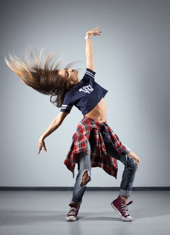 Bailarina hermosa joven moderna que presenta en un fondo del estudio