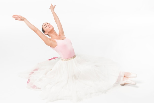 Bailarina joven bailarina con los ojos cerrados relajantes sobre fondo blanco
