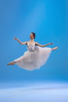 Bailarina joven y elegante en vestido blanco aislado en la pared azul