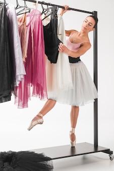 Bailarina joven de puntillas eligiendo vestido de perchas