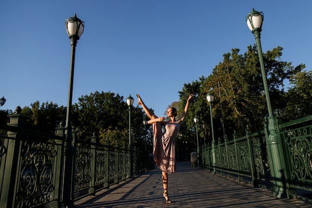 Bailarina a la luz del sol en un parque de la ciudad