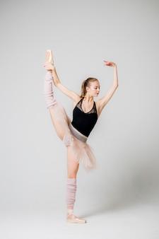 La bailarina mantiene el equilibrio de pie sobre una pierna.