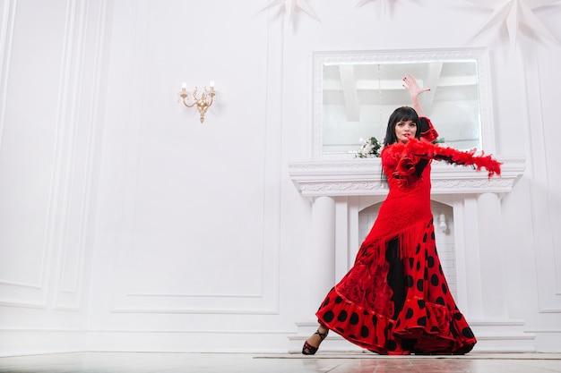 Bailarina de mujer en vestido rojo realizando danza folklórica gitana .foto con espacio para texto