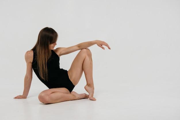La bailarina con el pelo largo y rubio con un leotardo de baile negro se sienta en el estudio sobre un fondo blanco.
