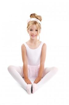 Bailarina pequeña bailarina de ballet infantil estirando sentado