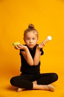 Bailarina perpleja eligiendo entre pera y helado