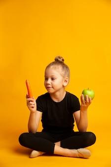 Bailarina perpleja eligiendo entre zanahorias y manzana verde