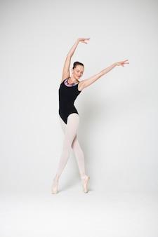 Bailarina está de pie en una pose de baile en pointes sobre un fondo blanco.