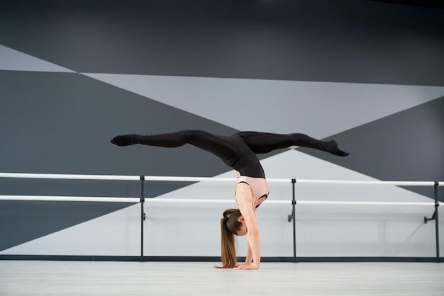 Bailarina de pie sobre los brazos mostrando split