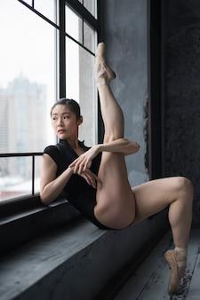 Bailarina posando junto a la ventana con la pierna arriba