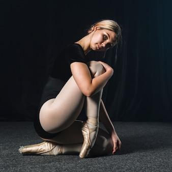 Bailarina posando de lado en leotardo y zapatillas de punta