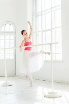Bailarina posando en zapatillas de punta en el pabellón de madera blanca
