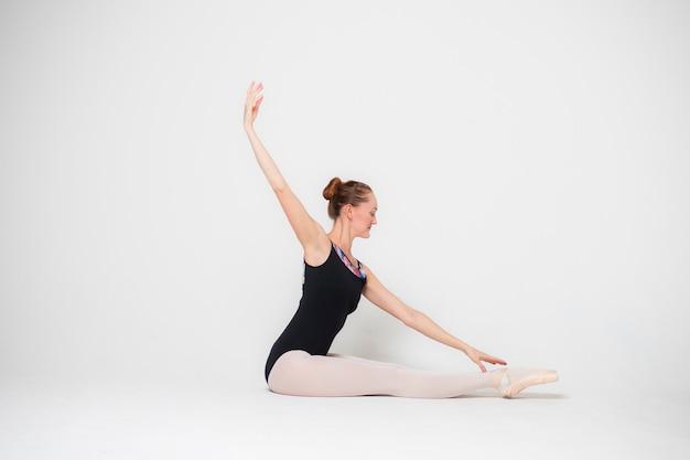 Bailarina en una pose sentada sobre un fondo blanco.