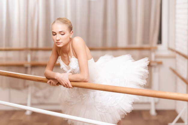 Bailarina profesional ensaya junto a la barra de ballet.