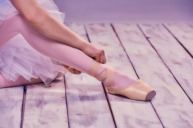 Bailarina profesional poniéndose sus zapatos de ballet