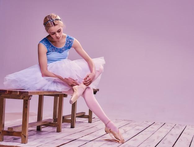 Bailarina profesional poniéndose sus zapatos de ballet.