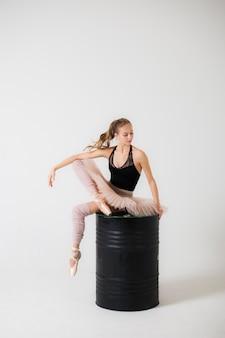 Bailarina está sentada en un barril negro sobre un fondo blanco.