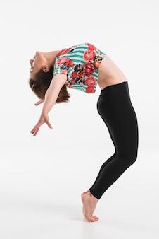 Bailarina de sexo femenino que realiza salto de la cadera aislado sobre el fondo blanco