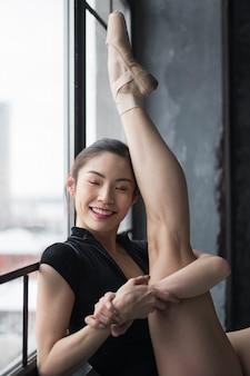 Bailarina sonriente posando con la pierna arriba