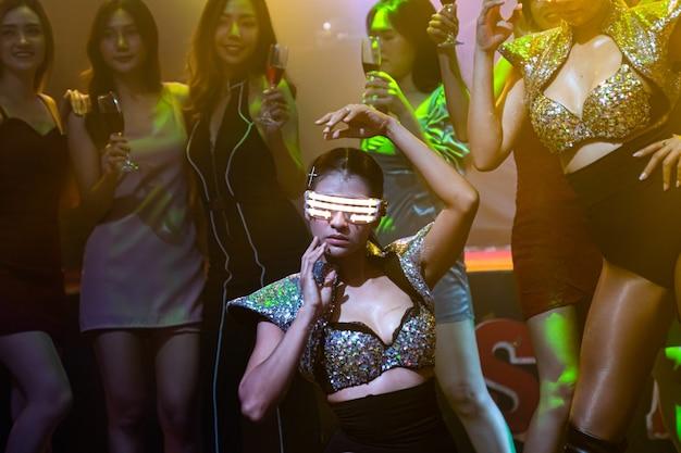 Bailarina de techno en club nocturno bailando al ritmo de la música de dj