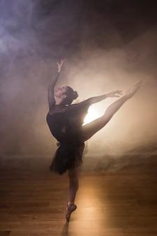 Bailarina de tiro completo en posición arabesca.