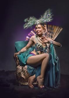 Bailarina en traje exótico se sienta en el sillón