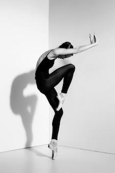 Bailarina en traje negro posando en zapatillas de punta