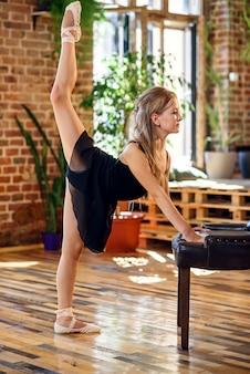 Bailarina en tutú negro haciendo ejercicios de estiramiento y calentamiento.