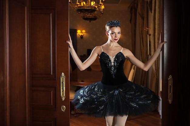 Bailarina en tutú negro de pie en la puerta