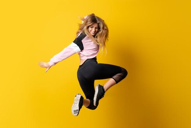 Bailarina urbana bailando sobre amarillo aislado y saltando.