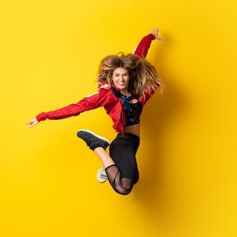 Bailarina urbana bailando sobre amarillo aislado y saltando