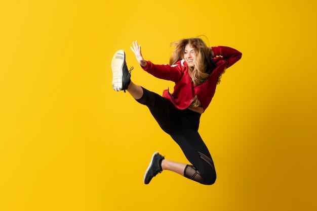 Bailarina urbana bailando sobre pared amarilla aislada y saltando