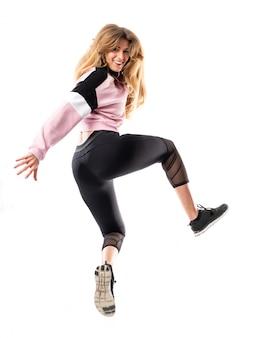 Bailarina urbana bailando sobre pared blanca aislada y saltando