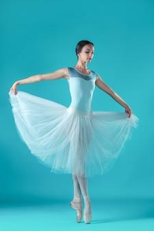 Bailarina en vestido blanco posando en dedos de los pies
