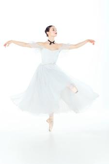 Bailarina en vestido blanco posando en zapatillas de punta, espacio de estudio.