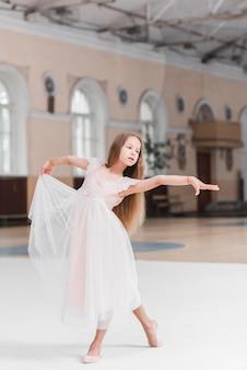 Bailarina en vestido rosa bailando en la pista de baile