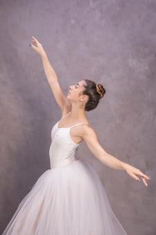 Bailarina de vista lateral con los brazos abiertos.