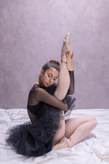Bailarina de la vista lateral que estira encima de su pierna