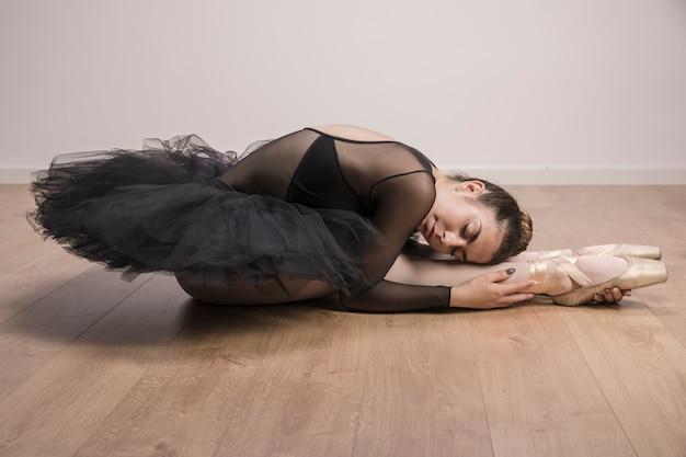 Bailarina de vista lateral sosteniendo sus piernas