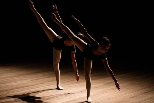 Las bailarinas flexibles se estiran en una escena oscura iluminada.