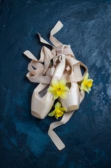 Bailarinas, zapatillas de punta sin gente sobre una superficie azul. flores de narciso amarillo.