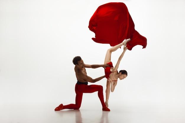 Bailarines de ballet clásico agraciado bailando aislado sobre fondo blanco de estudio. pareja con ropa de color rojo brillante como una combinación de vino y leche. el concepto de gracia, artista, movimiento, acción y movimiento.