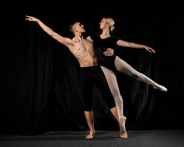 Bailarines de ballet posando con los brazos extendidos