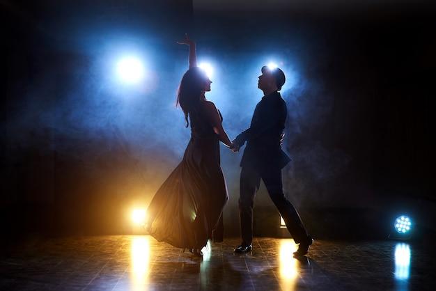 Bailarines expertos actuando en el cuarto oscuro bajo la luz del concierto y el humo. sensual pareja realizando una danza contemporánea artística y emocional